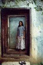Steve's favorite photo. Island girl in the doorway of the Japanese Headquarters building on Etten Island. Notice the bullet holes around the door.